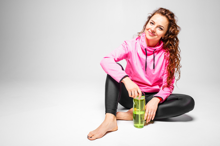 Young happy fit woman sitting with water bottle