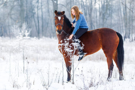 Young teenage girl with bay horse in winter park