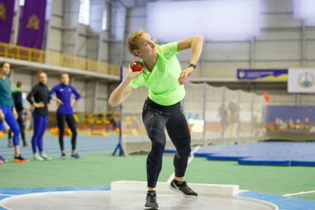 SUMY, UCRANIA - 9 DE FEBRERO DE 2018: Hanna Nelepa - realizando lanzamiento de peso en competencia de pentatlón en el campeonato ucraniano de atletismo bajo techo 2018 realizando salto de altura