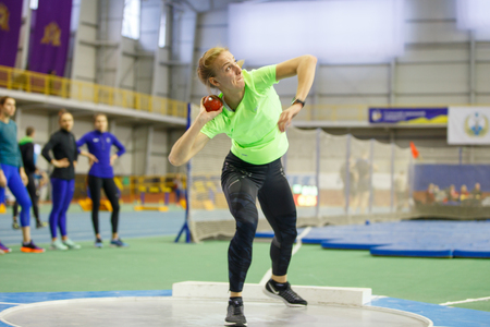 SUMY, 우크라이나 -2018 년 2 월 9 일 : Hanna Nelepa- 우크라이나 실내 육상 대회 2018 높은 점프를 수행하는 펜타 슬론 경쟁에서 퍼 팅 샷 수행