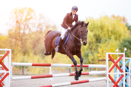 Young rider girl on bay horse jumping over barrier