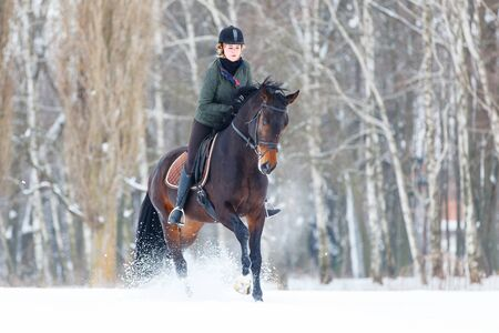 Young woman galloping on bay horse on winter field