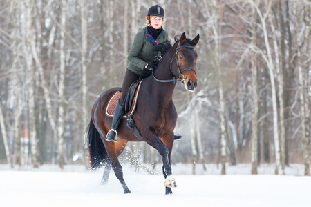 Young woman galloping on bay horse on winter field Stock Photo - 96933869