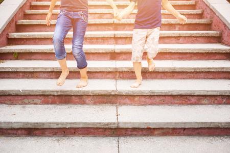 Children rushing down on stairs barefoot Stockfoto