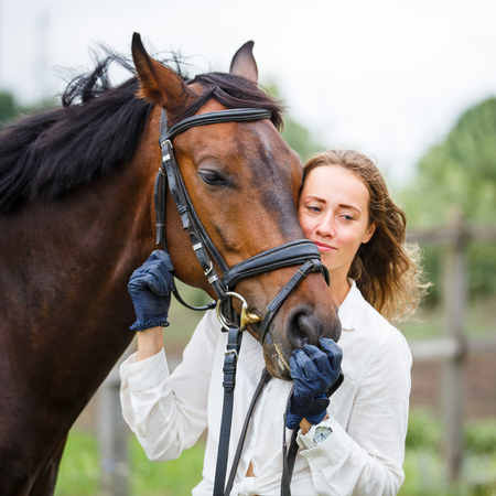 Young happy rider woman with her bay horse Stock Photo