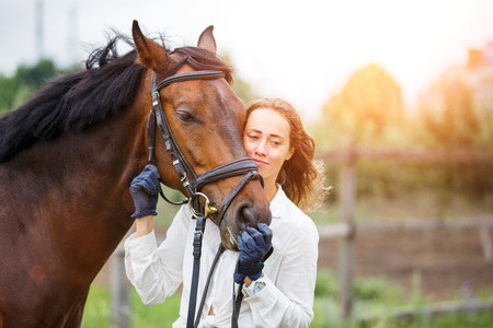 Young happy rider woman with her bay horse Stockfoto