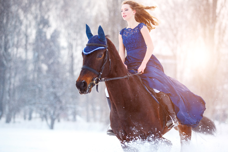 Young girl in dress riding horse on winter field