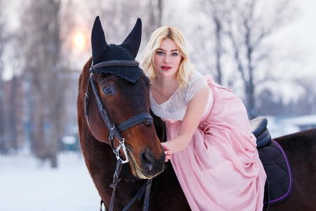 Young woman in dress riding horse on winter field
