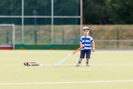 Piccolo ragazzo divertente che gioca hockey su prato Archivio Fotografico - 104184553