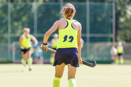 Young field hockey player girl with stick in the game. Back view