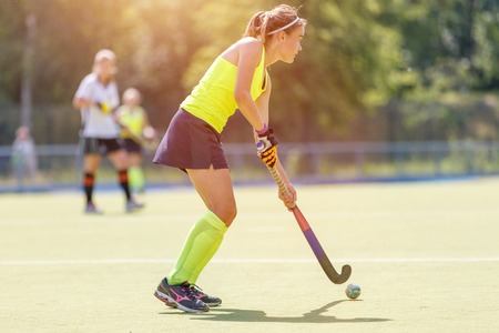 Young hockey player woman with ball in attack playing field hockey game Banque d'images - 121328286