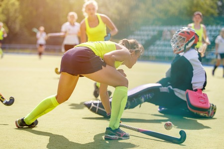 Young girl lead the ball into the net behind goalier in field hockey match