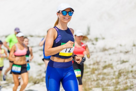 Junge schlanke Frau läuft Trail Race Contest kurz nach dem Start Standard-Bild