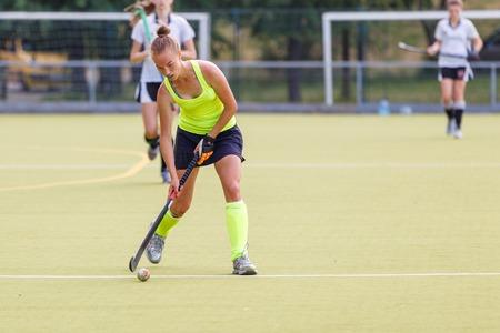 Donna giovane giocatore di hockey con palla in attacco