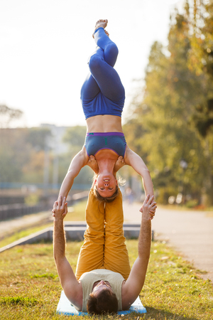 Couple of young man and woman practicing acro yoga in city park Imagens