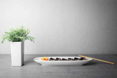 Maki sushi served in long plate on grey table