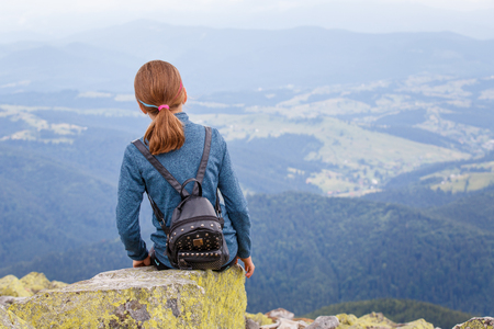 Teenage girl sitting on cliff in mountains
