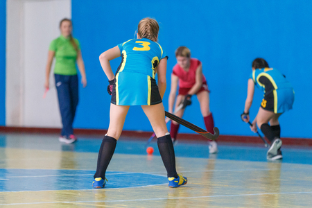 Young girls playing hockey. Indoor hockey training