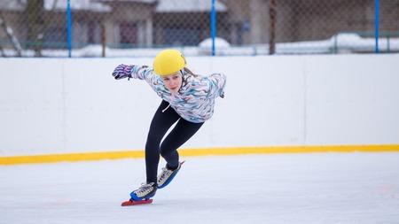 Snel schaatsend jong meisje op opleidingsbaan