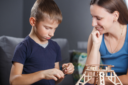 Young boy assembling constructor with his mother.