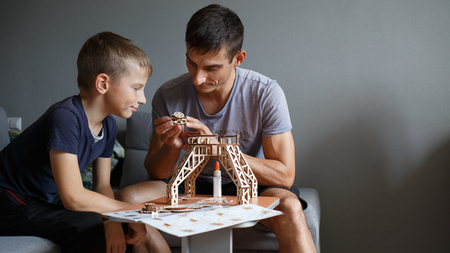 Young boy assembling constructor with his father Banco de Imagens