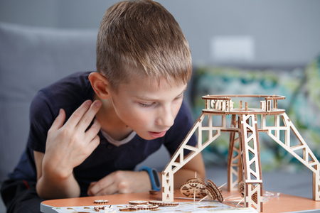 Young boy playing with eco wooden constructor