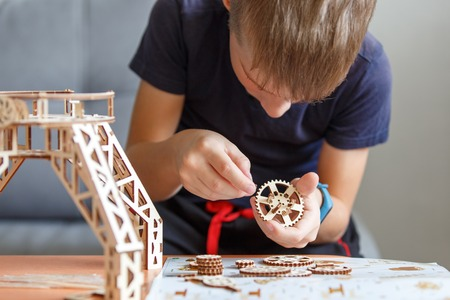 Young boy playing with eco wooden constructor Stock Photo
