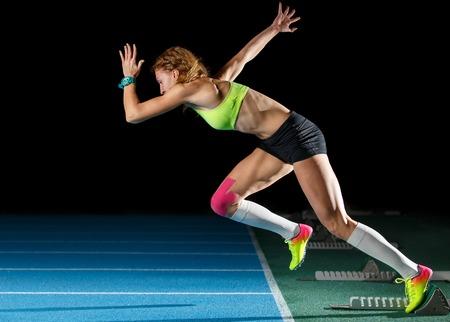 Atleta femminile che inizia la sua corsa sprint Archivio Fotografico