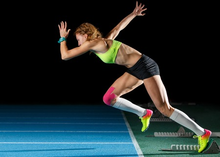 Female athlete starting her sprint race running Stock Photo