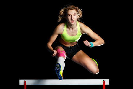 Jeune athlète féminine sautant par-dessus l'obstacle en sprint