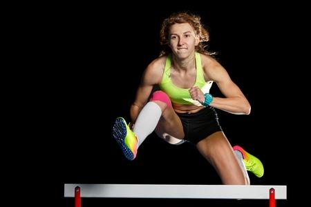 Jeune athlète féminine sautant par-dessus l'obstacle en sprint Banque d'images