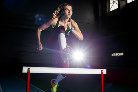 Young sportswoman running and jumping over hurdle