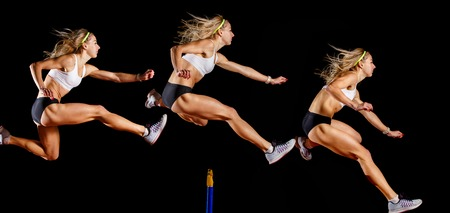 Sportswoman jumping over hurdle on sprint race