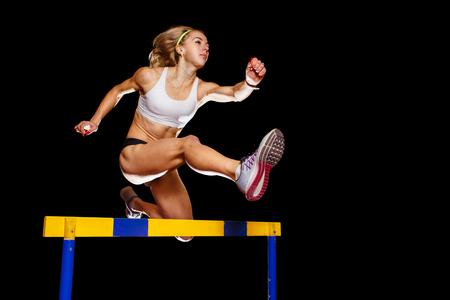 Sportive sautant par-dessus l'obstacle sur la course de sprint