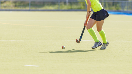 Young female field hockey player leading ball in attack. Foto de archivo - 121330058
