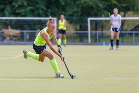 Young female field hockey player leading ball in attack.