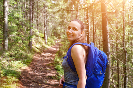 Young happy backpacker woman walking in woods