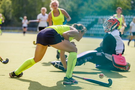 Young girl lead the ball into net in hockey match