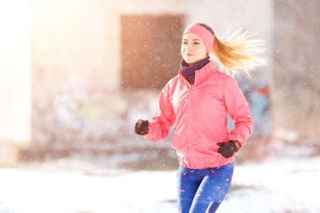 Young slim woman jogging in winter park. Smiling girl running in cold weather