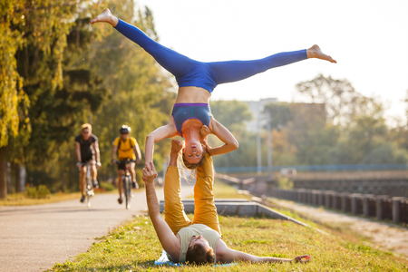Couple of young man and woman practicing acro yoga