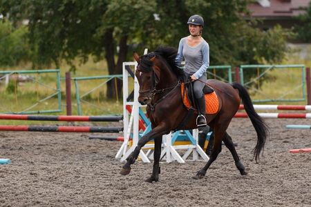 Young girl riding bay horse on show jumping training Imagens