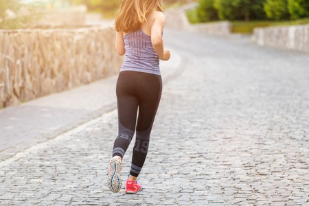 Back view of running woman on cobbled road with copy space aside