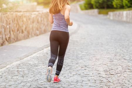 Widok z tyłu biegnącej kobiety na brukowanej drodze z kopią miejsca na bok