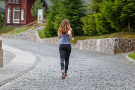 Back view of running woman on cobbled road with copy space aside Stock fotó