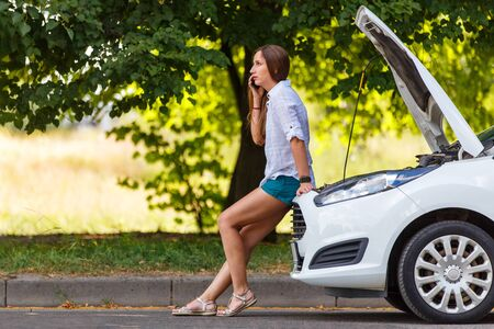 Young woman in trouble calling for help at the broken car Standard-Bild