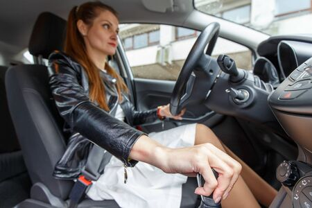 Young woman in leather jacket and white dress driving a car. Female driver holding hand on gear stick Фото со стока