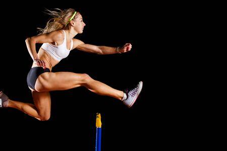 Sportiva muscolare che salta sopra l'ostacolo sulla corsa di sprint isolata su fondo nero Archivio Fotografico