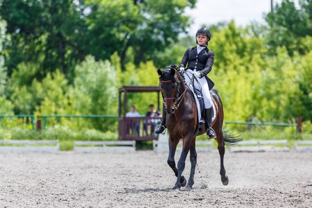 Young woman riding horse on dressage advanced test