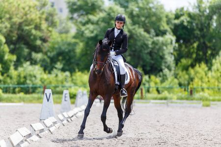 Young woman riding horse on dressage advanced test Stock Photo