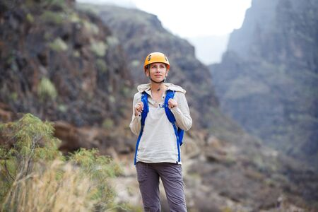 Young woman with backpack enjoying mountains on trekking trip in volcanic ravine on Tenerife, Spain